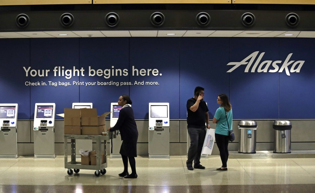 People stand in the Alaska Airlines ticket area at Sea-Tac International Airport Friday, Aug. 10, 2018, in SeaTac, Wash. An airline mechanic stole an ...