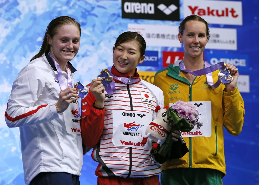 Japan's Rikako Ikee, center, poses with her medal on the podium after winning the women's 100m butterfly final, with second-placed Kelsi Dahlia of the