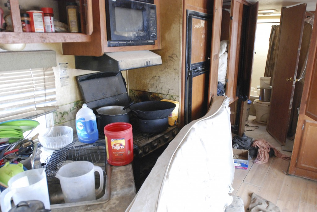 Various items litter the kitchen of a makeshift living compound in Amalia, N.M., on Friday, Aug. 10, 2018, where five adults were arrested on child ab...