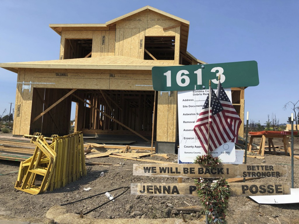 In this Friday, August 10, 2018, photo, signs and flags mark the partially rebuild home of Debbie and Rick Serdin in the Coffey Park neighborhood of S