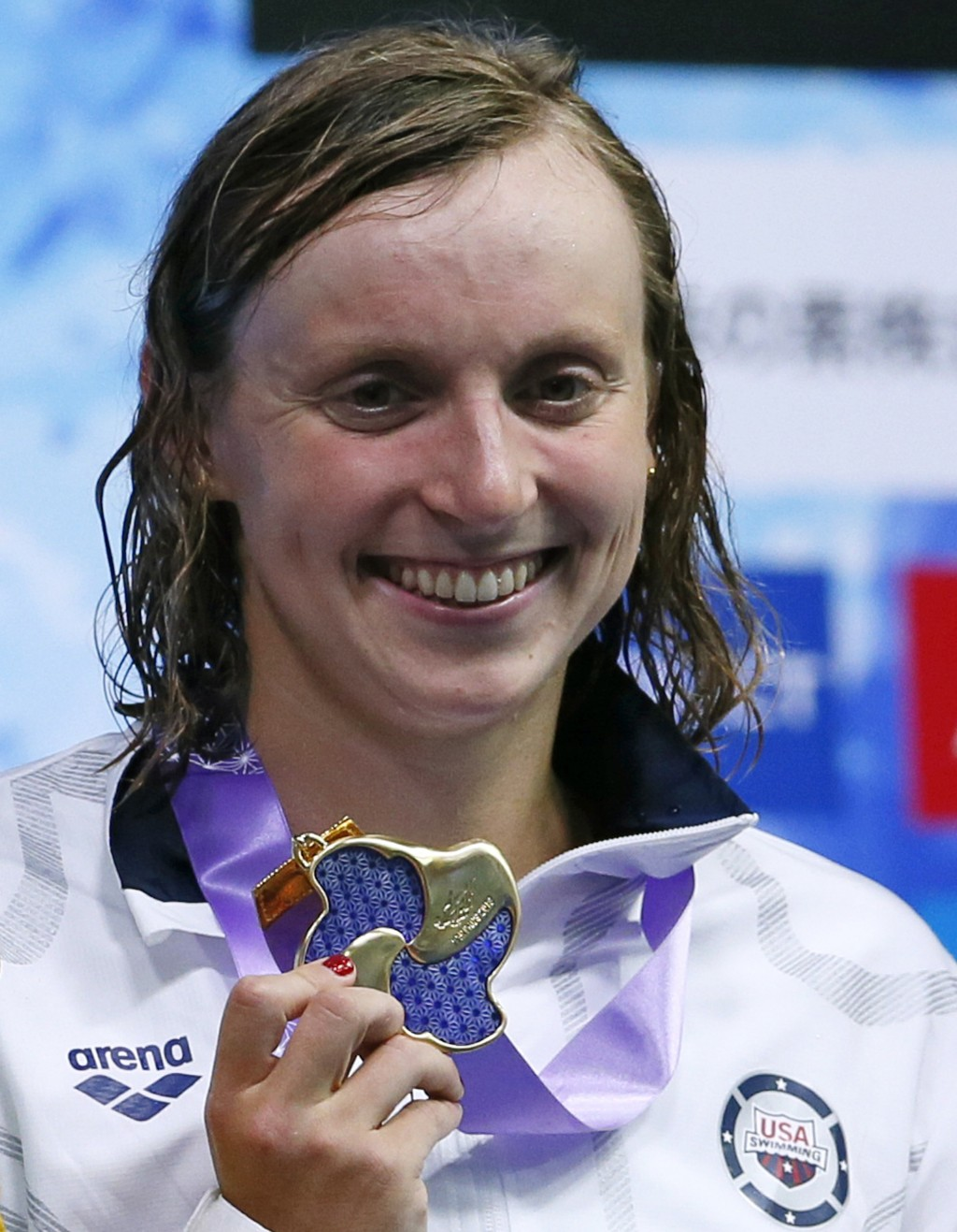 U.S. swimmer Katie Ledecky poses with her medal on the podium after winning the women's 400m freestyle final during the Pan Pacific swimming champions