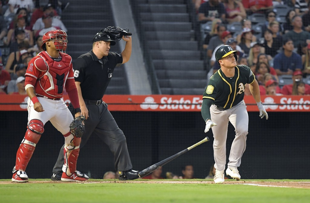 Oakland Athletics third baseman Matt Chapman, right, drops his bat as he hits a solo home run as Los Angeles Angels catcher Jose Briceno, left, and ho