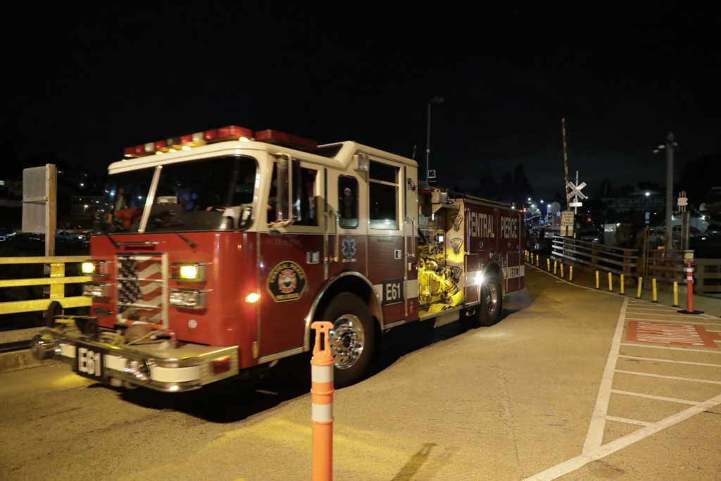 Ffire trucks drive toward a ferry boat headed to Ketron Island, Friday, Aug. 10, 2018, at the ferry terminal in Steilacoom, Wash. An airline mechanic ...