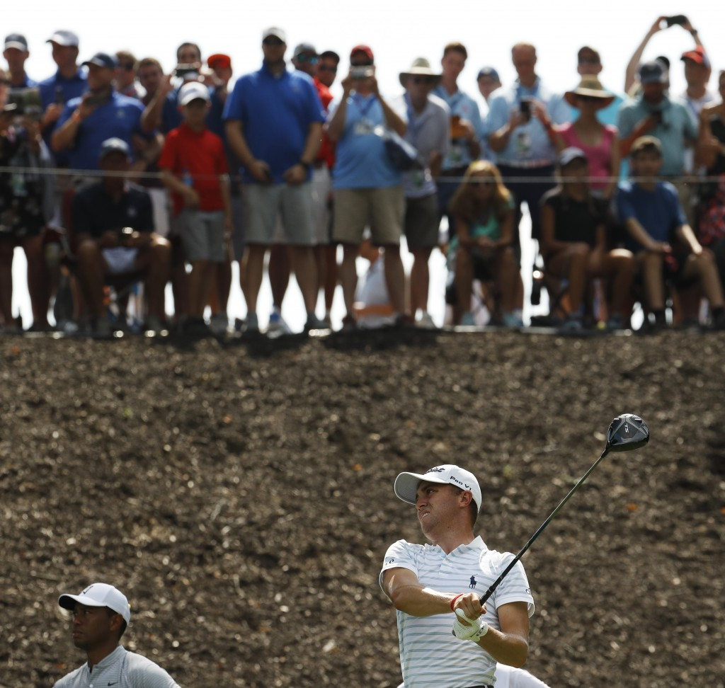 Spectators watch from above as Justin Thomas drives on the eighth hole as Tiger Woods watches at lower left, during the second round of the PGA Champi