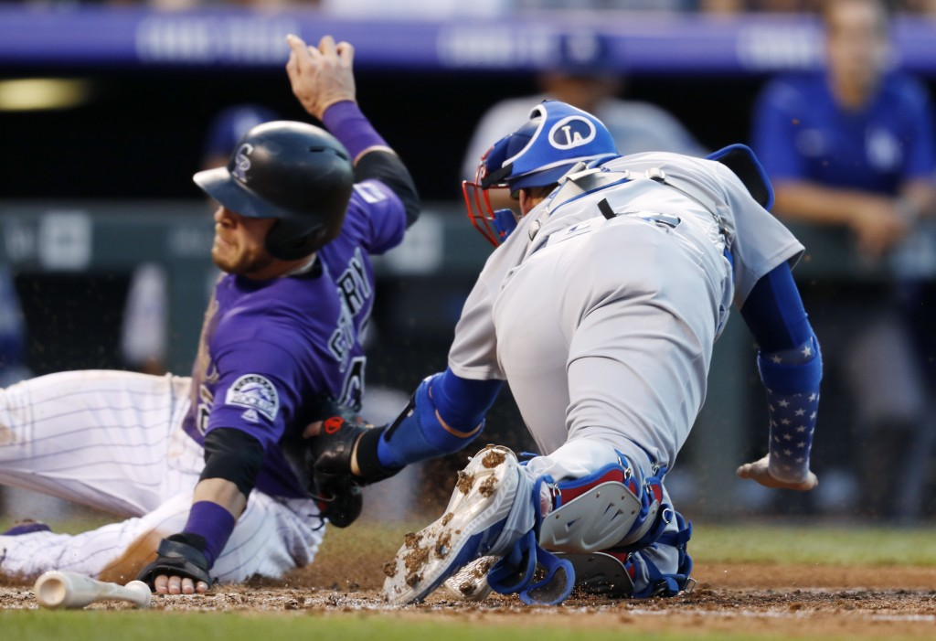 Los Angeles Dodgers catcher Yasmani Grandal, right, tags out Colorado Rockies' Trevor Story as he tried to score from third base on a ground ball hit