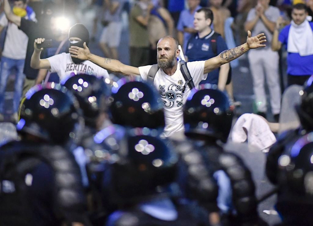 A man stands in front of a riot police line during protests outside the government headquarters, in Bucharest, Romania, Friday, Aug. 10, 2018. Romania