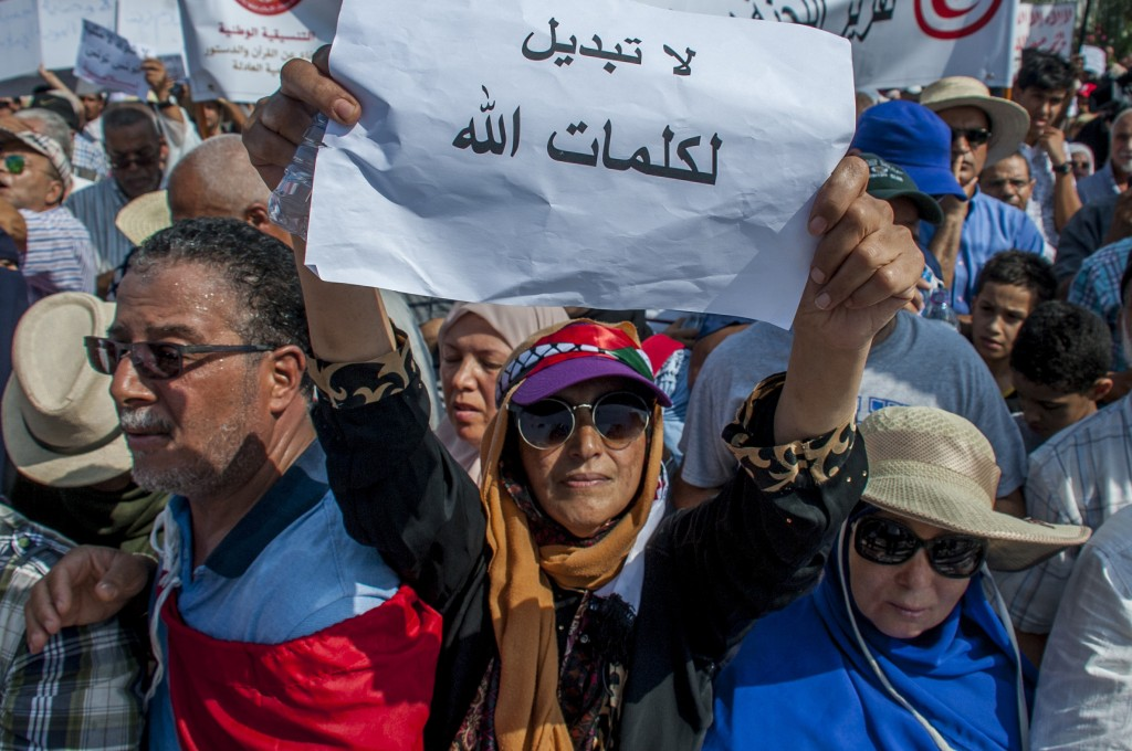 "People demonstrate, one with a poster reading ""No to change God's speech"" during a demonstration in Tunis, Saturday Aug 11, 2018. Thousands of Muslim"