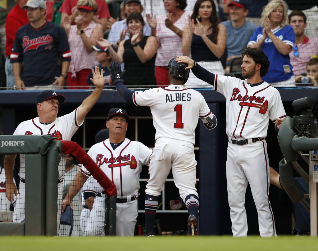 Atlanta Braves' Ozzie Albies (1) is greeted at the dugout entrance by hitting coach Kevin Seitzer, left, manager Brian Snitker and Dansby Season after