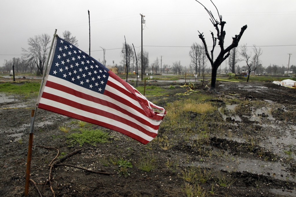 FILE - In this April 6, 2018, file photo, a U.S. Flag is placed on a wildfire-ravaged property as rain comes down in the the Coffey Park area in Santa