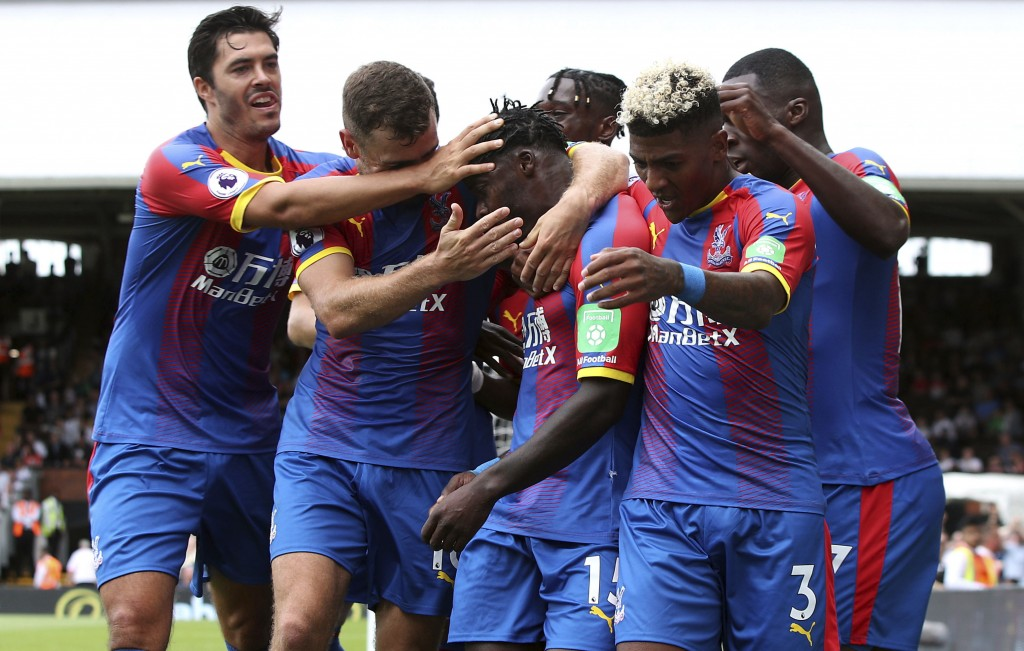 Crystal Palace's Jeffrey Schlupp, centre, is congratulated after scoring his side's first goal of the game against Fulham during their English Premier