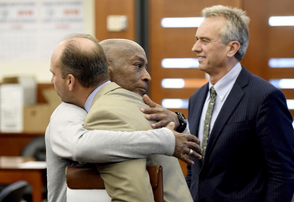 Dewayne Johnson, center, hugs one of his attorneys, next to lawyer and member of his legal team Robert F Kennedy Jr., right, after the verdict was rea