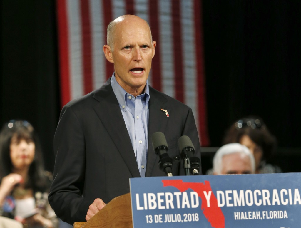 FILE- In this July 13, 2018 file photo, Florida Gov. Rick Scott, speaks to Cuban-American supporters at a campaign stop, in Hialeah, Fla. Scott, calli