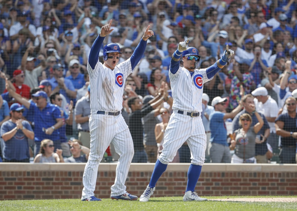 Chicago Cubs' Anthony Rizzo, left, and Javier Baez, right, celebrate after scoring on single hit by Jason Heyward against the Washington Nationals dur