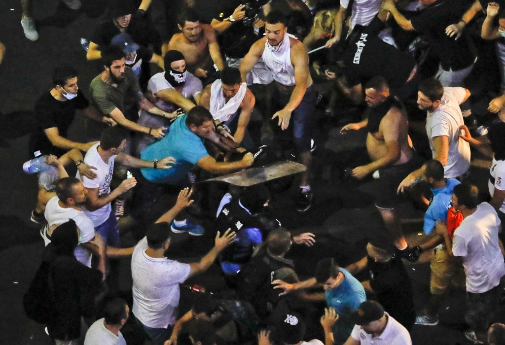 People mob riot police officers who fell and were left behind during a charge to clear the square during protests outside the government headquarters,