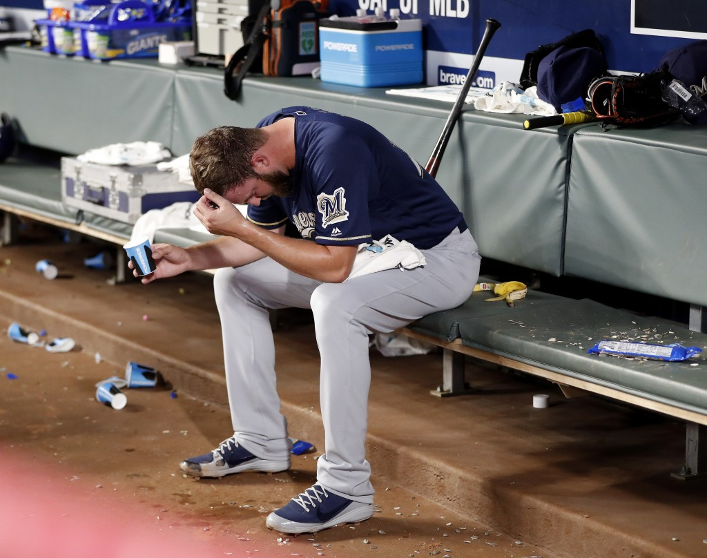 Milwaukee Brewers relief pitcher Jordan Lyles sits in the dugout after being relieved in the sixth inning of a baseball game against the Atlanta Brave