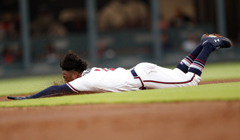 Atlanta Braves' Ozzie Albies slides as he steals second base in the first inning of a baseball game against the Milwaukee Brewers, Friday, Aug. 10, 20
