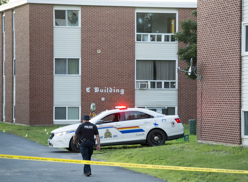 An Royal Canadian Mounted Police officer walks on the scene at an apartment building in Fredericton, New Brunswick, Canada, on Friday, Aug. 10, 2018.