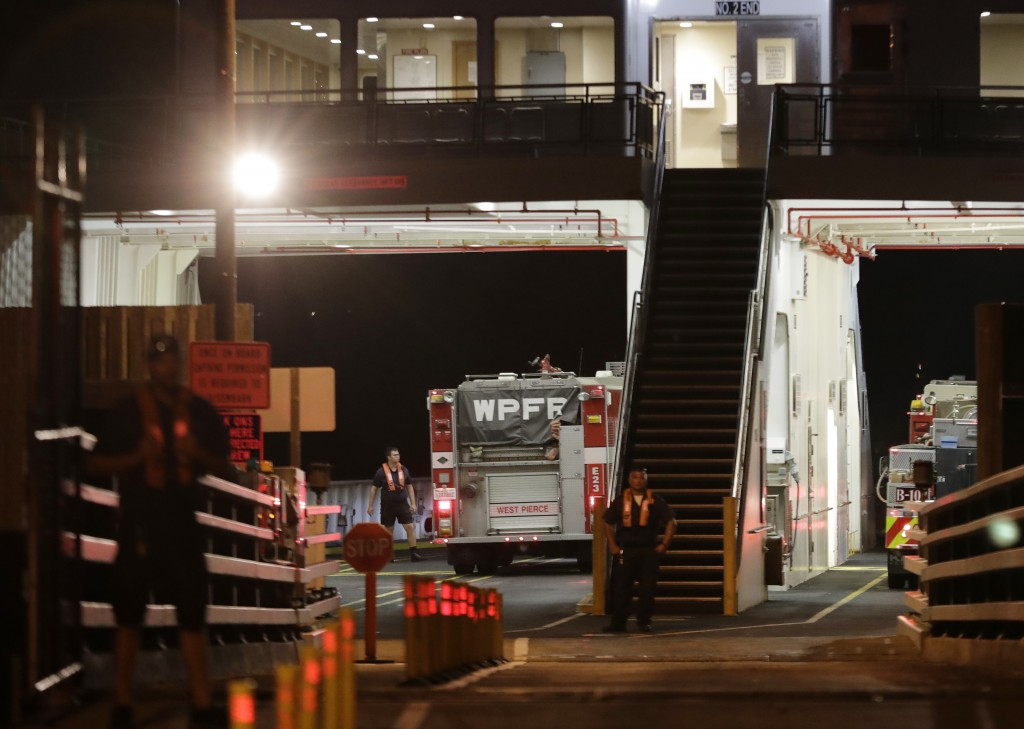 Ferry workers stand by as fire trucks are parked on a ferry boat headed to Ketron Island, Friday, Aug. 10, 2018, at the ferry terminal in Steilacoom, ...