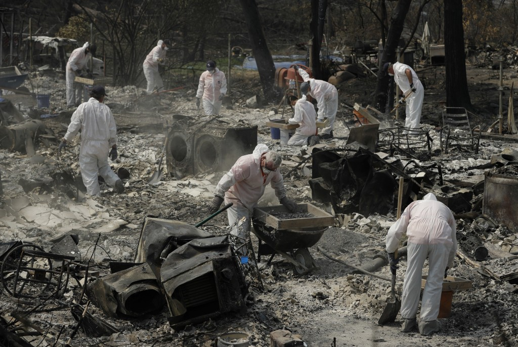 Volunteers with Samaritan's Purse sift through the charred remains of a home burned in the Carr Fire, Friday, Aug. 10, 2018, in Redding, Calif. (AP Ph...