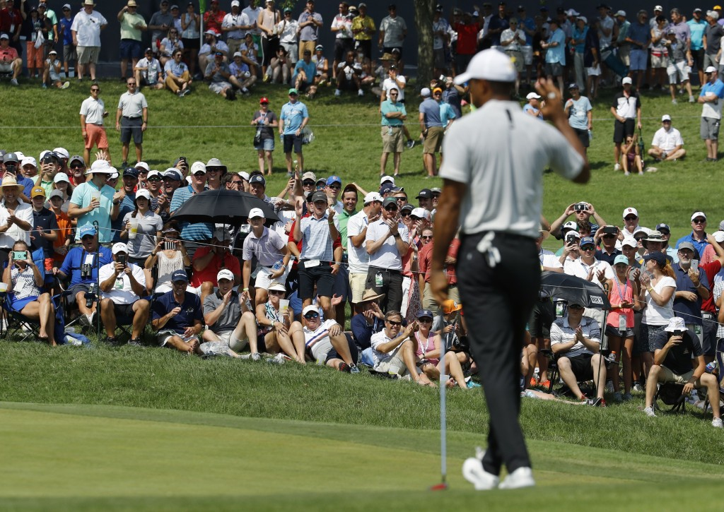 Fans cheer after Tiger Woods made par on the sixth hole during the second round of the PGA Championship golf tournament at Bellerive Country Club, Fri