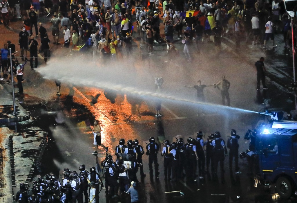 Riot police use a water canon during a charge to clear the square during protests outside the government headquarters, in Bucharest, Romania, Friday,