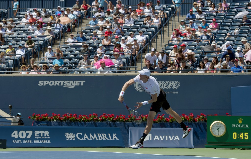 Kevin Anderson of South Africa serves in front of sparsely filled stands on his way to defeating Grigor Dimitrov of Bulgaria during Rogers Cup quarter