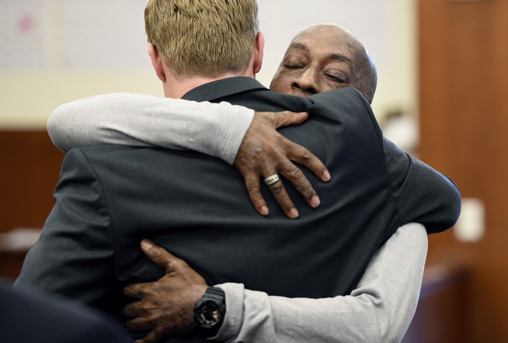 Plaintiff Dewayne Johnson, facing camera, hugs one of his lawyers after hearing the verdict in his case against Monsanto at the Superior Court of Cali