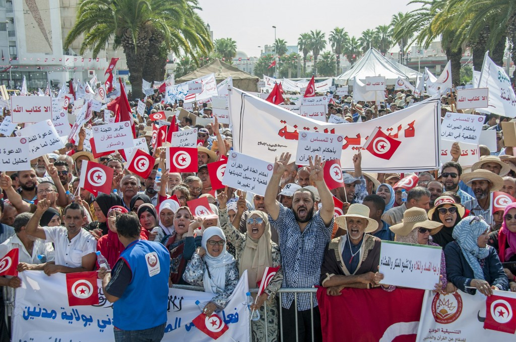 People demonstrate in Tunis, Saturday Aug 11, 2018. Thousands of Muslim fundamentalists have held an hours-long protest in front of the nation's parli