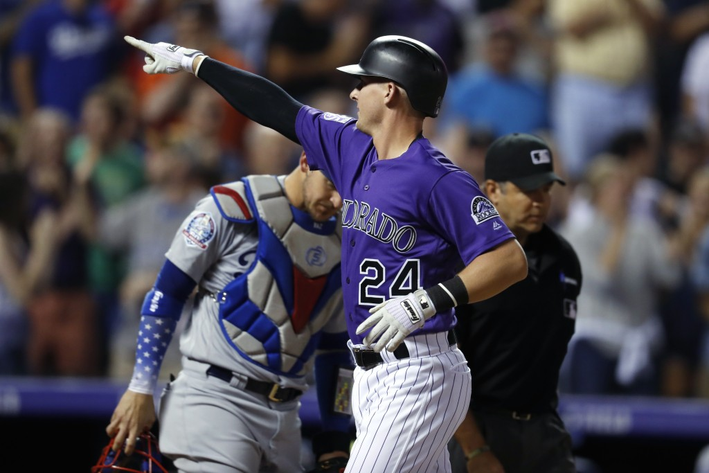 Colorado Rockies' Ryan McMahon, front, gestures as he crosses home plate after hitting a two-run home run, next to Los Angeles Dodgers catcher Yasmani