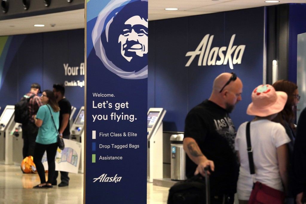People stand in the Alaska Airlines ticket area at Sea-Tac International Airport Friday, Aug. 10, 2018, in SeaTac, Wash.An airline mechanic stole an A