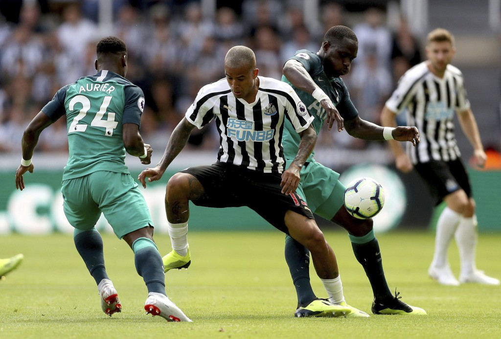Newcastle United's Kenedy, centre, struggles between Tottenham Hotspur's Serge Aurier, left, and Moussa Sissoko during their English Premier League so