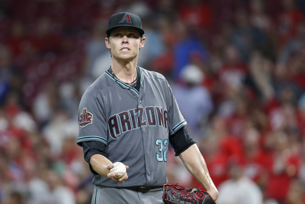 Arizona Diamondbacks starting pitcher Clay Buchholz reacts after giving up an RBI bunt single to Cincinnati Reds' Billy Hamilton during the seventh in