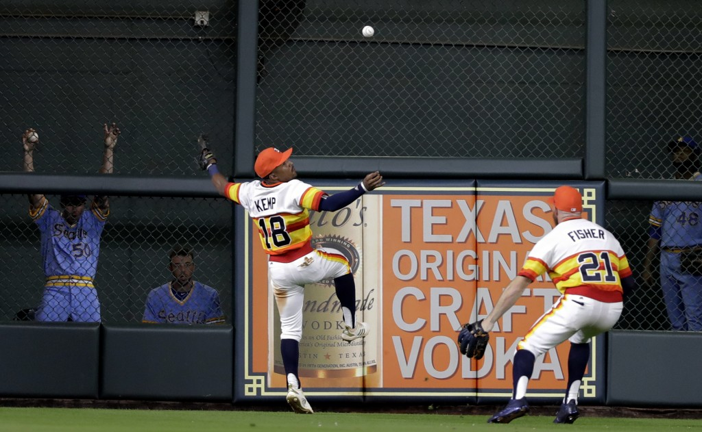 Houston Astros outfielders Tony Kemp (18) and Derek Fisher (21) chase a two-run double by Seattle Mariners' Nelson Cruz during the eighth inning of a