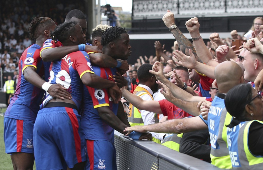 Crystal Palace's Jeffrey Schlupp, centre, celebrates with fans and teammates after scoring his side's first goal of the game against Fulham, during th