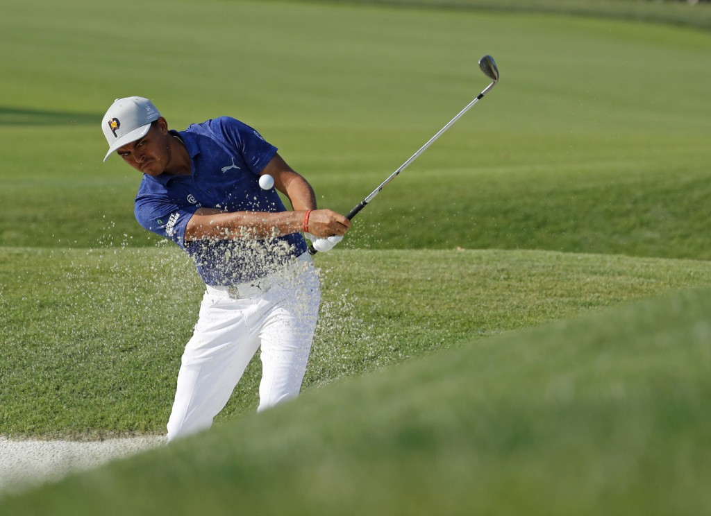 Rickie Fowler hits out of a bunker to the 18th green during the second round of the PGA Championship golf tournament at Bellerive Country Club, Saturd