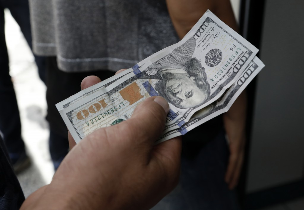 A Turkish waits to change his US dollars with Turkish liras inside a currency exchange shop in Ankara, Turkey, Friday, Aug. 10, 2018. A financial shoc...