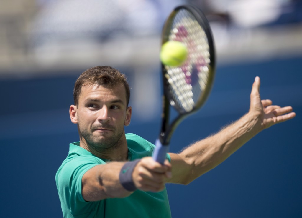 Grigor Dimitrov of Bulgaria hits a backhand on his way to being defeated by Kevin Anderson of South Africa during Rogers Cup quarterfinal tennis tourn