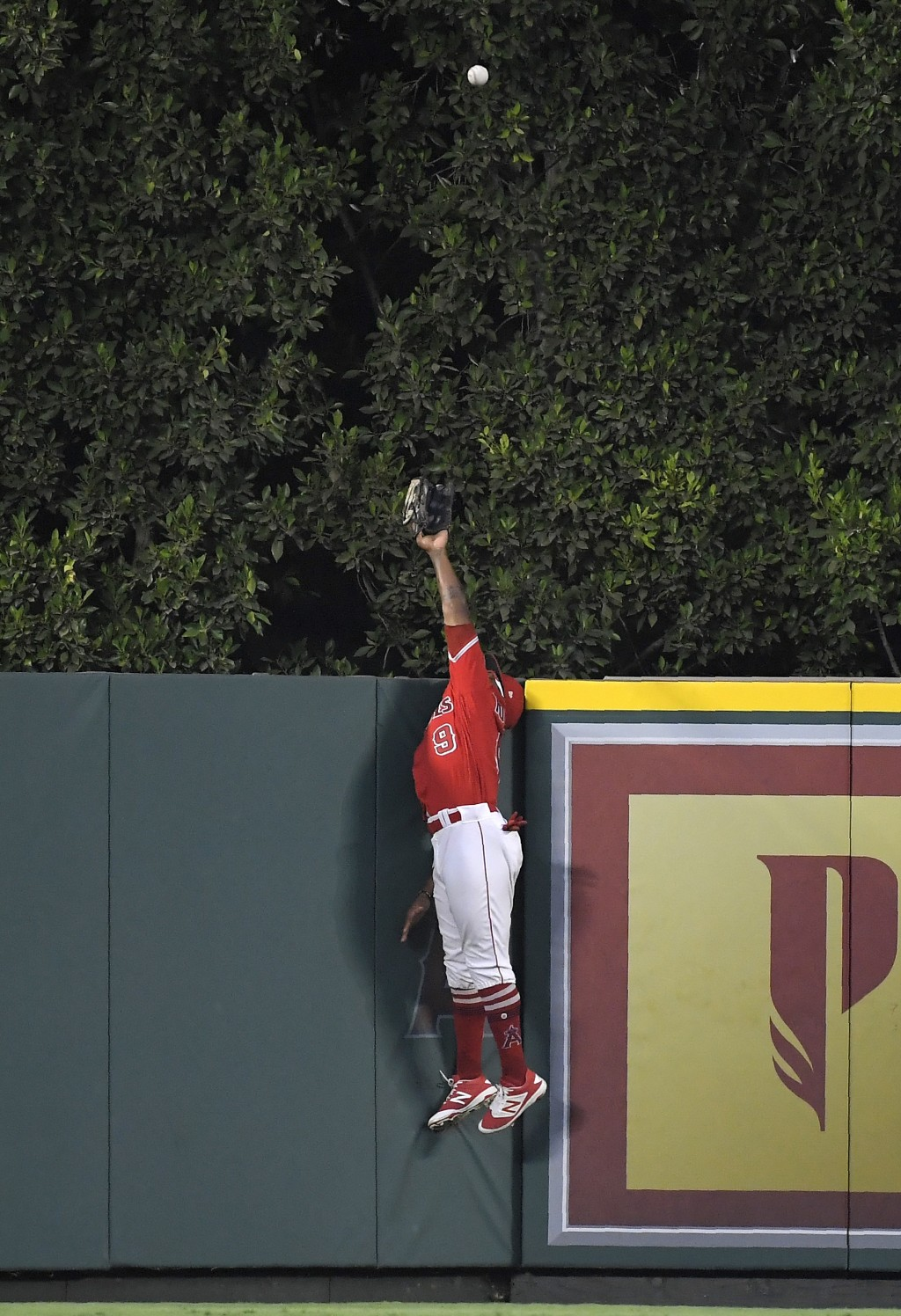 Los Angeles Angels center fielder Eric Young Jr. can't reach a solo home run by Oakland Athletics' Khris Davis during the first inning of a baseball g