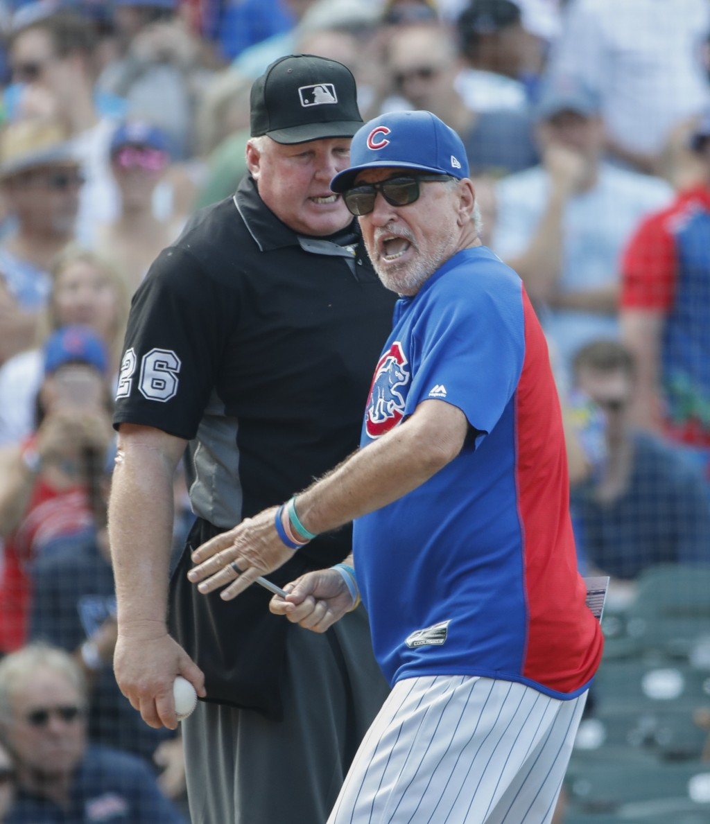 Chicago Cubs manager Joe Maddon, right, argues a call against his team with umpire Bill Miller, left, as he is ejected from a baseball game against th