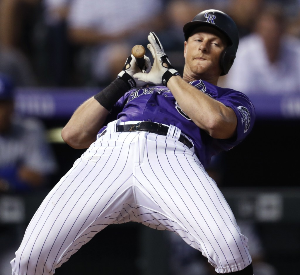 Colorado Rockies' DJ LeMahieu avoids a high, inside pitch from Los Angeles Dodgers starter Kenta Maeda during the fourth inning of a baseball game Fri