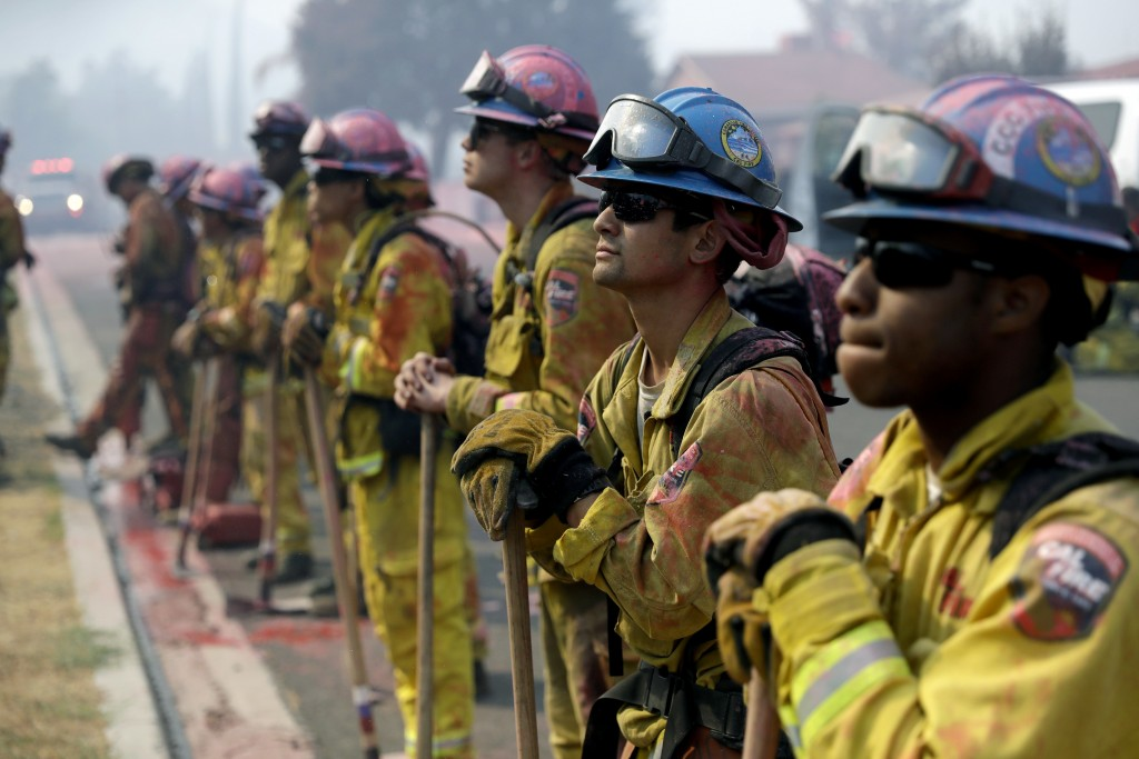 Fire crews line up as they watch a wildfire on a ridge top while protecting a residential area Friday, Aug. 10, 2018, in Lake Elsinore, Calif. (AP Pho