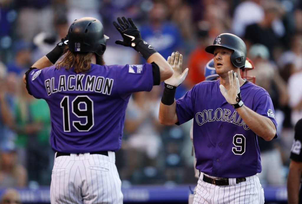 Colorado Rockies' Charlie Blackmon, left, congratulates DJ LeMahieu, who crosses home plate after hitting a two-run home run off Los Angeles Dodgers s