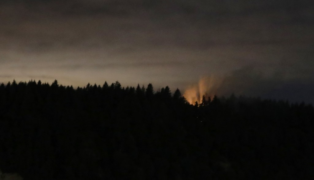 In this long-exposure photo, smoke and an orange glow are seen on Ketron Island in Washington state, early Saturday, Aug. 11, 2018 as viewed from near...