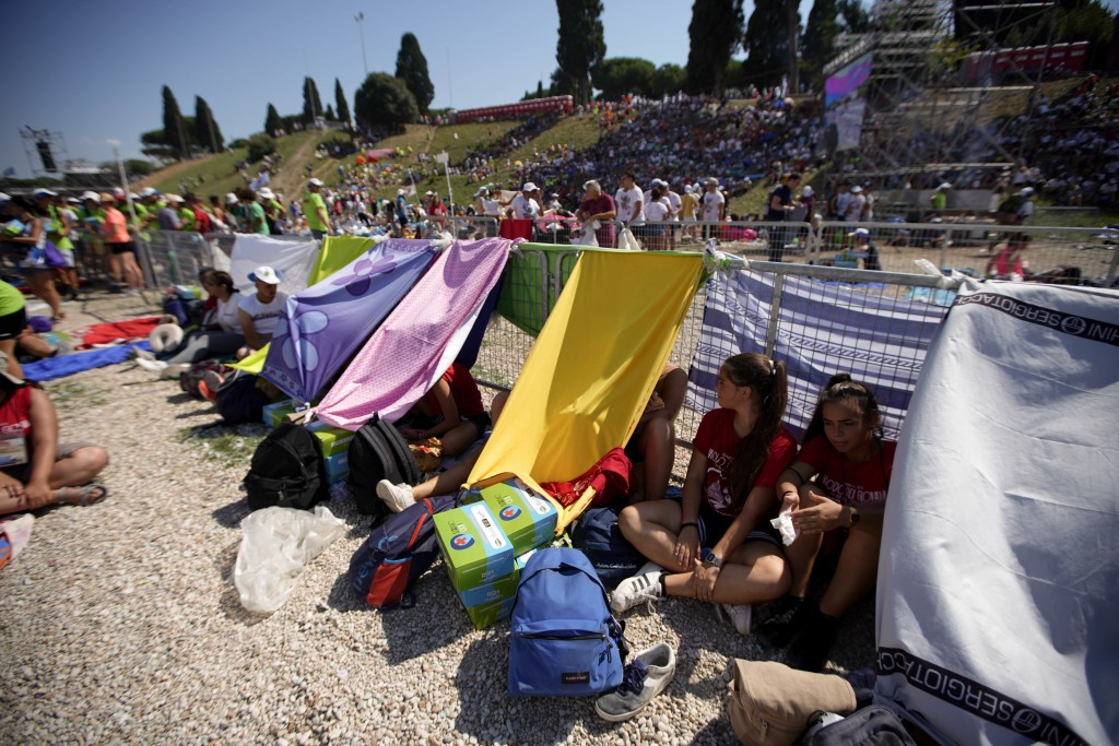 Faithful gather in Rome's Circus Maximus as they wait for the arrival of Pope Francis to lead an evening prayer vigil with youths, Saturday, Aug. 11,