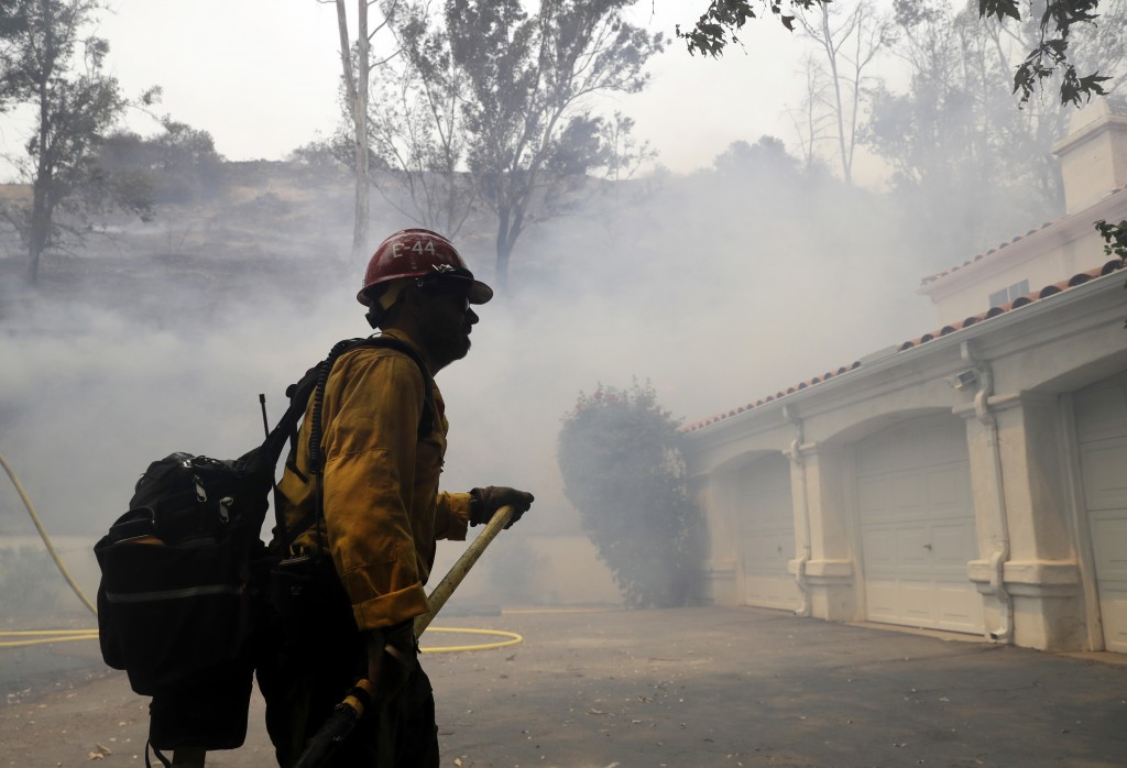 A firefighter walks in front of a home as smoke from an advancing wildfire fills the air Friday, Aug. 10, 2018, in Lake Elsinore, Calif. Firefighters ...