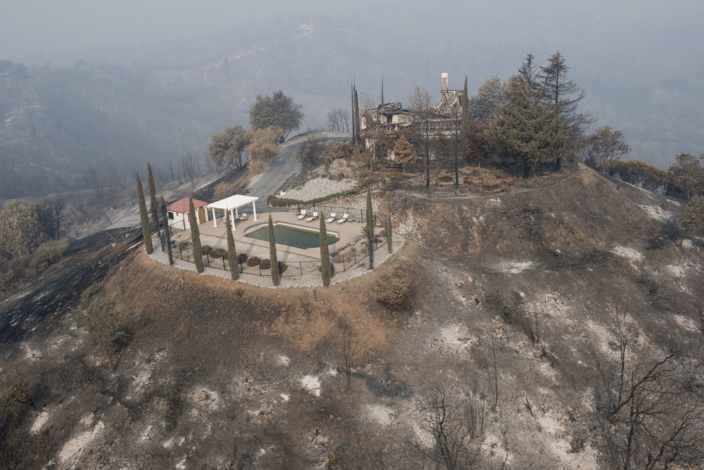 A swimming pool is all that remains of a hilltop home after being burned by a wildfire that swept through Shasta County an area west of Redding, Calif