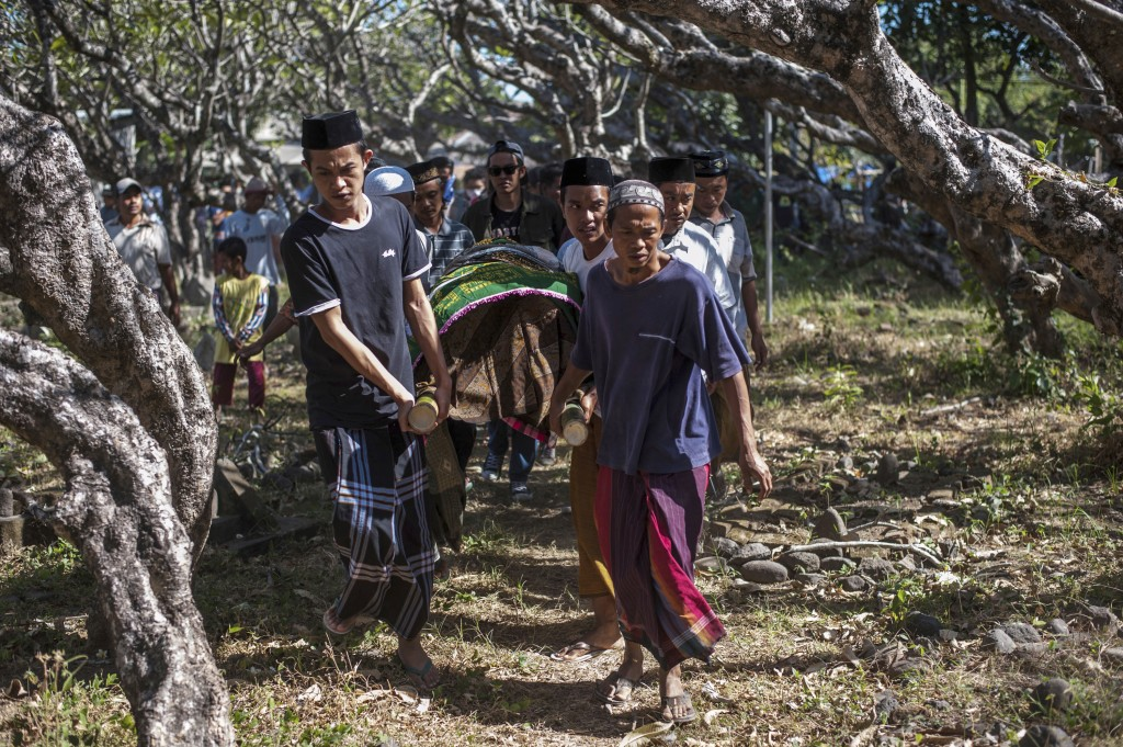 Indonesian men carry the body of a victim of last week's earthquake during a burial in Gangga, Lombok Island, Indonesia, Sunday, Aug. 12, 2018. Hundre...