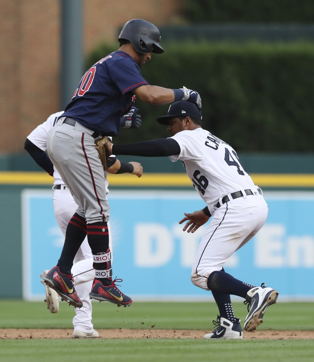 Minnesota Twins' Eddie Rosario, front left, is caught in a rundown by Detroit Tigers third baseman Jeimer Candelario, right, during the sixth inning o