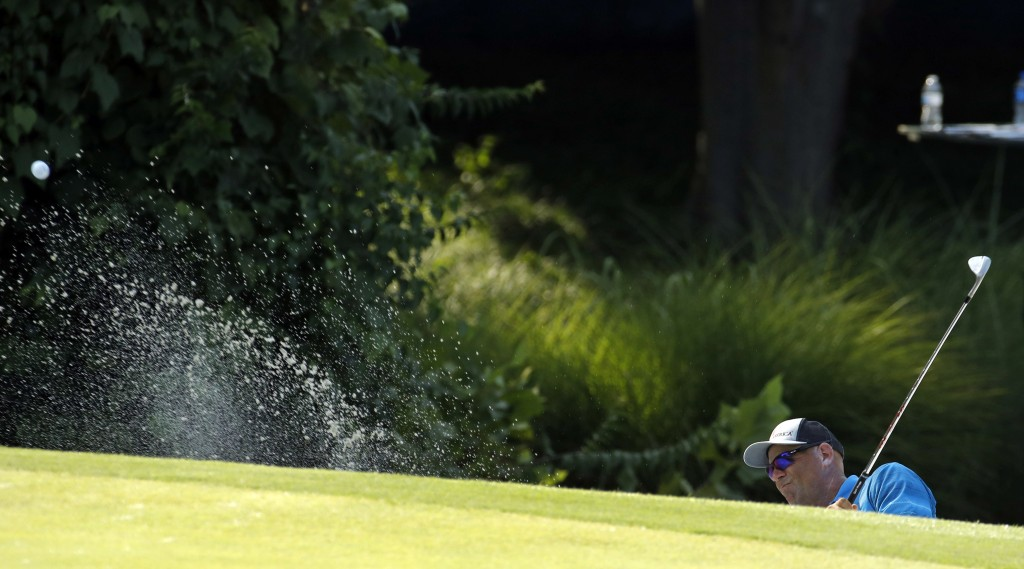 Stewart Cink hits out of a bunker on the 17th hole during the third round of the PGA Championship golf tournament at Bellerive Country Club, Saturday,