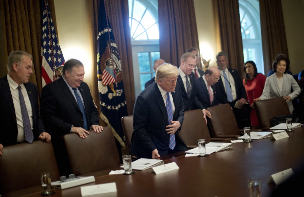 In this July 18, 2018, file photo, President Donald Trump, center, takes his seat before the start of his meeting with members of his Cabinet in the C...